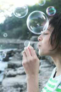 photography of woman blowing bubbles
